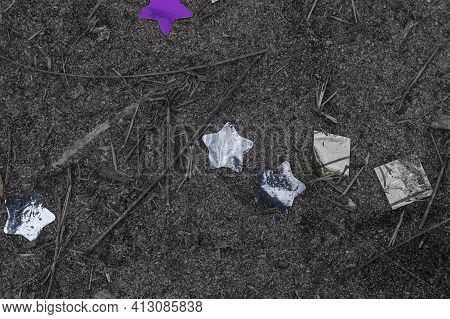 Glittery Holiday Tinsel In The Shape Of Stars On The Ground. Lilac And Silver Confetti Among The San