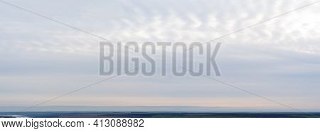 Panorama Of Cloudy Gray Sky With Blurred Horizon Line, Fields And Meadows In The Distant Background,
