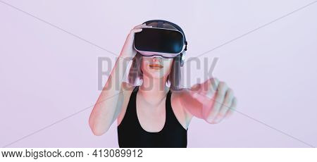 Caucasian Girl Playing With Virtual Reality Goggles Pointing With Her Hand Out Of Focus To The Camer