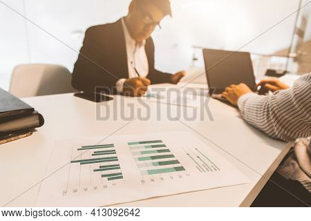 Young Office Worker Sitting At Desk, Using Computer. Two Business Man Talking