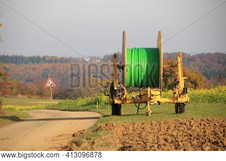 Trailer With A Roll Of Empty Conduit For Laying Cables In The Ground