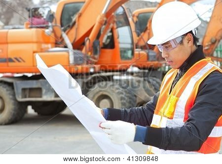 Road Construction Worker With Heavy Equipment On The Background
