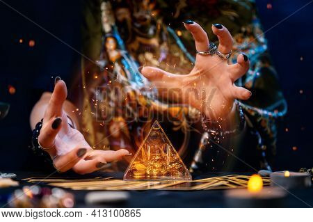 A Fortune Teller Conjures A Glass Pyramid. Magical Aura And Sparks Around The Pyramid. Close-up. The