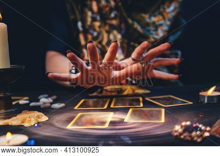 Astrology. The Sorceress Conjures Over The Tarot Cards Spread Out On The Table. Hands Close-up. The
