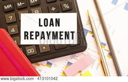 Text Loan Repayment On White Card With Metal Pen, Calculator And Financial Charts. Business And Fina