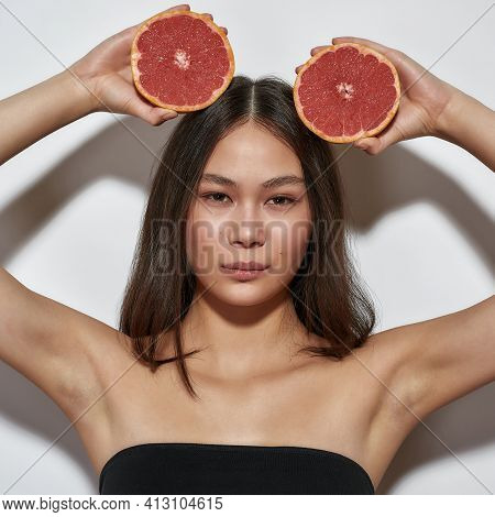 Beautiful Girl Standing In The Studio With Grapefruits. Young Girl With Clean Skin On A Light Backgr