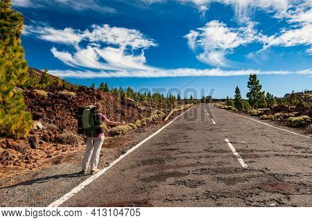 Young Woman Hiker With Backpack From Behind Standing On Wayside Of Road And Hitchhiking Near Pico De