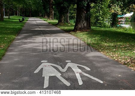 Two Silhouettes Of A Woman And A Child On An Empty Footpath In A Park.. Parental Guidance Concept -