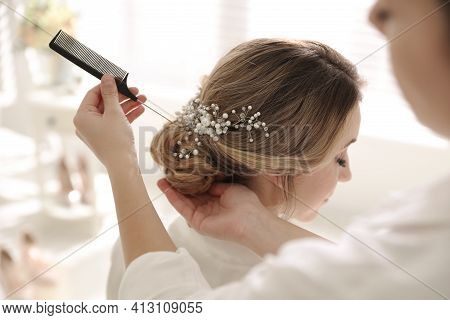 Professional Stylist Making Wedding Hairstyle For Bride In Salon
