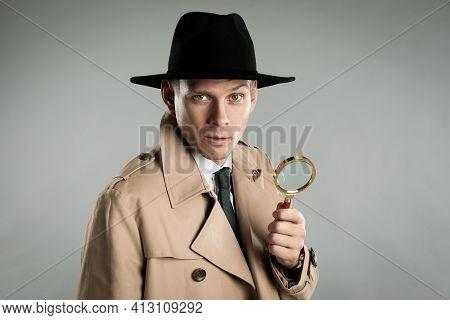 Male Detective With Magnifying Glass On Grey Background