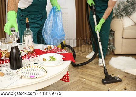 Cleaning Service Team Working In Messy Room After New Year Party, Closeup