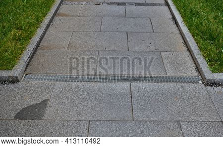 Across The Path There Is A Channel With A Metal Grid For Drainage Interlocking Paving. The Water Is
