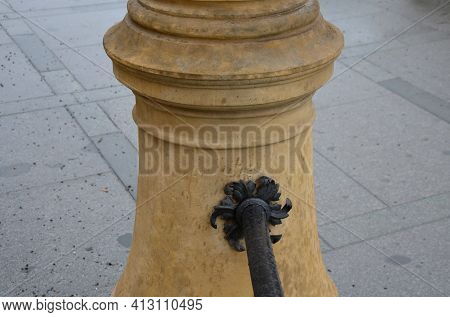 Railing On The Stairs With An Orange Yellow Plaster Foot Column. The Railing Is Made Of A Black Meta