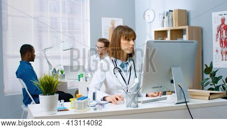 Caucasian Young Female Physician Working In Medical Center Sitting At Desk Typing On Computer At Wor