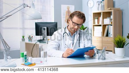 Portrait Of Middle-aged Happy Positive Handsome Caucasian Male Doctor In Glasses Working In Hospital