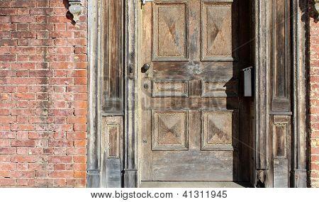 Old weathered wood door in brick wall