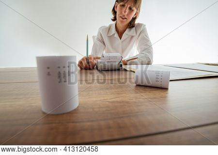 Young Female Accountant Using Adding Machine Working At Her Desk Full Of Printout Receipts And Docum