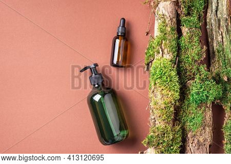 Unlabelled Cosmetic Bottle On Brown Background, Natural Moss Over Branches, Bark. Skin Care, Organic