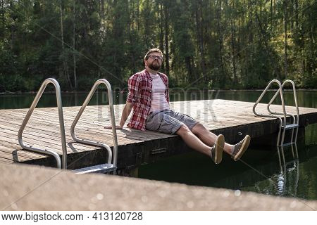 Calm Man Sits On The Edge Of A Wooden Pier And Looks Up Thoughtfully, Against The Background Of A Ca