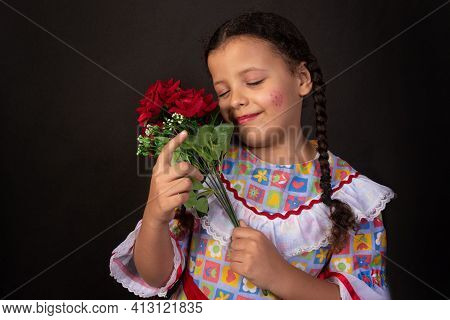 Festa Junina In Brazil, Brazilian Girl With Braids And Dressed For Junina Party With Bouquet Of Flow