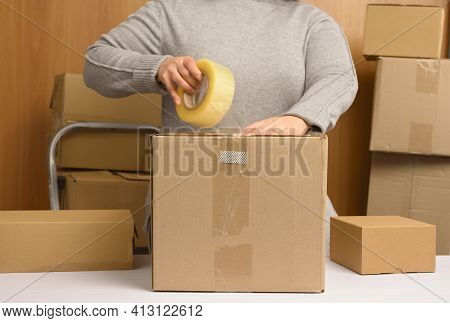 Woman In A Gray Sweater Holds A Roll Of Duct Tape And Packs Brown Cardboard Boxes On A White Table,