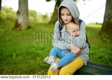 Cute Big Sister Admiring Her Baby Brother. Adorable Teenage Girl Holding Her New Baby Boy Brother. K
