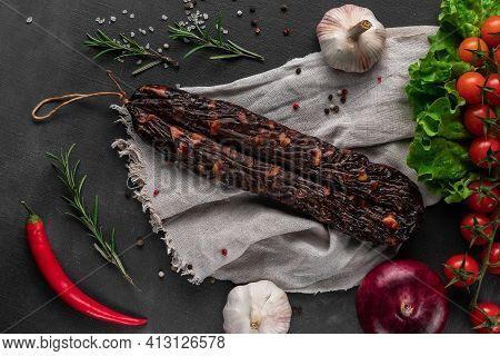 Bunch Of Red Dry Homemade Sausage On A Dark Background, Garlic And Sackcloth, Top View