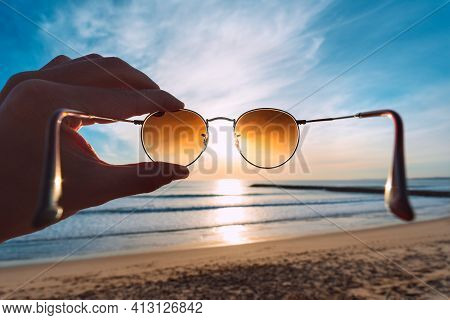 Hand Holding Stylish Round Sunglasses With Brown Lenses At Sunset. Putting On Sunglasses At Sunny Su