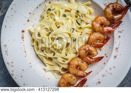 Close Up Seafood Tagliatelle Pasta With Grilled Shrimps, Bechamel Sauce And Thyme, Fettuccine Pasta.