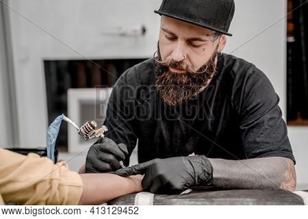 Male Tattoo Master Tattooing Female Client. Tattoo Machine And Lamp. Workplace Artist. Creating Pict