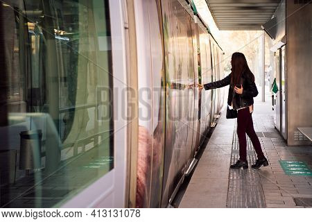 Young Woman Pressing The Door Button To Open The Door And Board The Streetcar, Concept Of Public Tra
