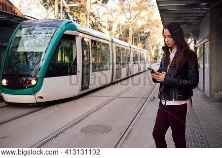 Woman Consulting Her Telephone At The Streetcar Stop, Concept Of Technology And Public Transportatio
