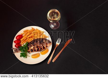 Delicious Roasted Dorado  Fish And Glass Of White Wine On Dark Background. View From Above, Copy Spa