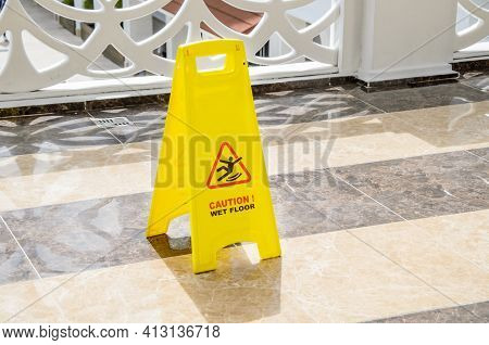 Yellow Warning Sign Caution Wet Floor On A Marble Floor In A Public Area. Preventing Injuries To Hot