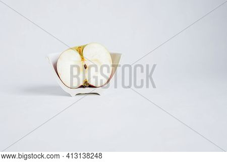 Concept. Sliced half Of An Apple In A Broken Half Of A Ceramic Small Plate On A White Background.