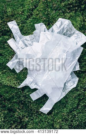 Disposable Plastic Bags On Green Moss, Grass Background. Pollution Problem Concept. Top View. Copy S