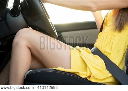 Close Up Of Young Woman Driver Fastened By Seatbelt With Long Legs In Yellow Summer Dress Behind Ste