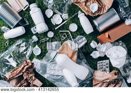 Plastic Waste, Food Packaging, Trash Collection On Green Moss Background After Picnic In Forest. Pla