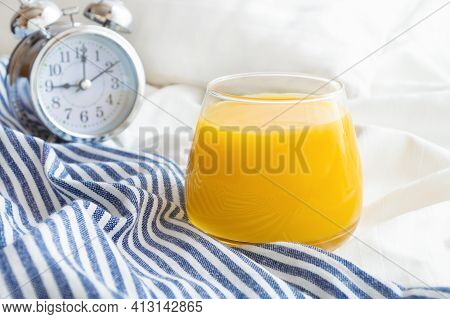 Glass Of Orange Juice And Alarm Clock On Bed With White Linen And Blue Bedspread. Good Morning Conce