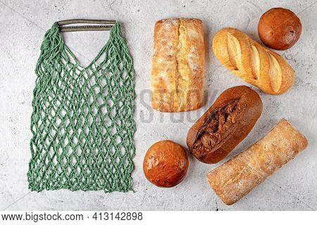 Baking Background With Eco String Bag And Whole Fresh Baked Loaves Of Bread Top View On Gray Backgro
