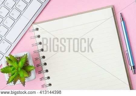 Open Blank Diary With Keyboard Computer On Pink Background.