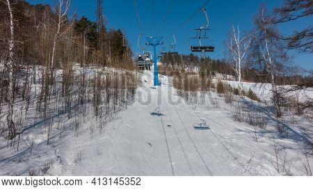 The Chairlift Over The Winter Forest Rises Up The Hill. Bare Branches Of Trees Against The Blue Sky.