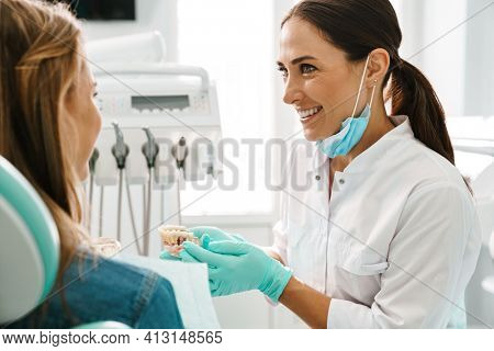 European mid happy dentist woman showing teeth imitation to her patient in dental clinic