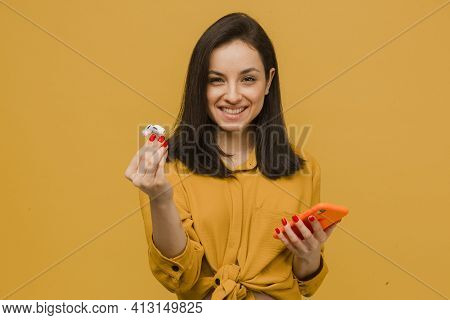 Photo Of Young Female Holds Earpods And Smartphone Looks So Kind And Happy. Wears Yellow Shirt, Isol