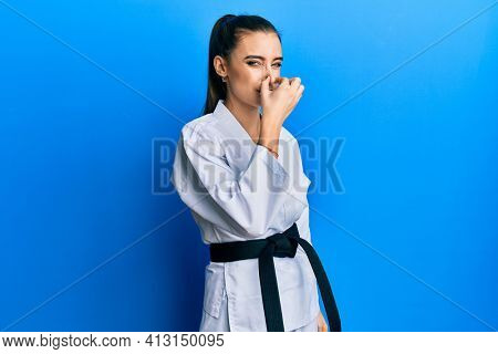 Beautiful brunette young woman wearing karate fighter uniform with black belt smelling something stinky and disgusting, intolerable smell, holding breath with fingers on nose. bad smell