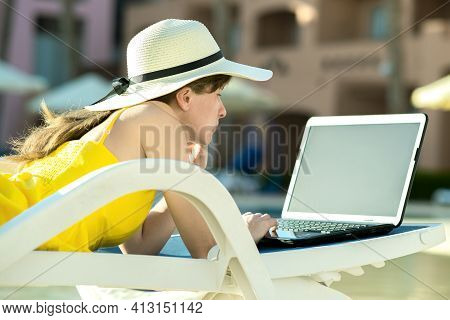 Young Woman On Beach Chair At Swimming Pool Working On Computer Laptop Connected To Wireless Interne