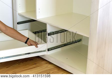 Close Up Of Carpenter Hands Installing Wooden Drawer On Sliding Skids In Contemporary Cupboard Cabin