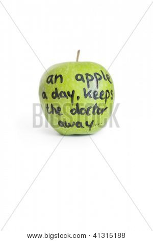 Close-up of sayings text on a juicy granny smith apple over white background