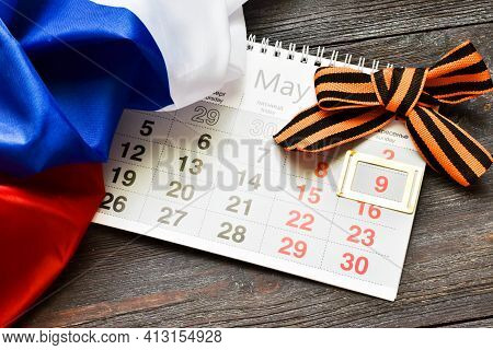 May 9. St. George Ribbon, Calendar With Date 9 In Frame And Russia Flag On A Wooden Background. The