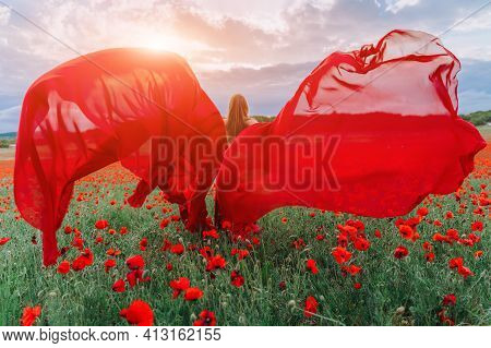 A Young Woman In A Red Dress And Long Red Wings Poses In A Large Field Of Red Poppies At Sunset